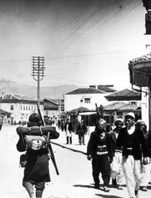 """Italian soldiers passing Albanians, 7 April 1939"" by DIREKTOR via Wikimedia Commons (Public domain)"